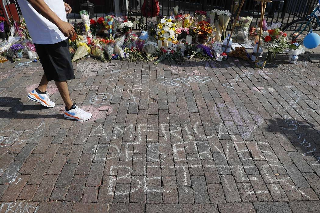 A pedestrian passes a makeshift memorial for the slain and injured victims of a mass shooting t ...