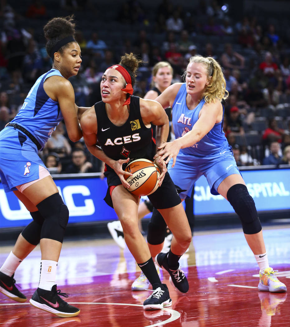Las Vegas Aces' Dearica Hamby, center, looks to shoot under pressure from Atlanta Dream's Nia C ...