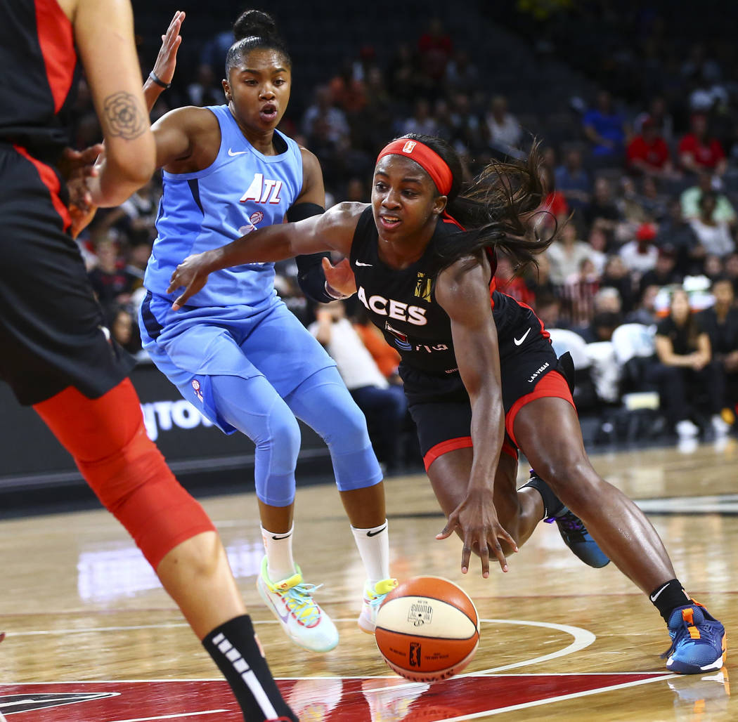 Las Vegas Aces' Jackie Young drives the ball past Atlanta Dream's Alex Bentley during the secon ...