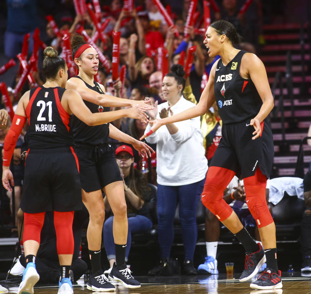 Las Vegas Aces' Liz Cambage, right, celebrates with teammates Kayla McBride (21) and Dearica Ha ...