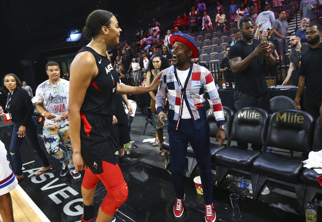 Las Vegas Aces' Liz Cambage talks with boxer Floyd Mayweather after a WNBA basketball game at t ...