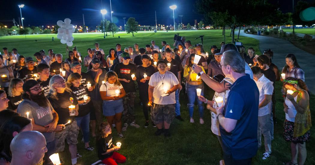 Mourners gather and listen to Jason Deborski speak during a candlelight vigil for Harlee Debors ...