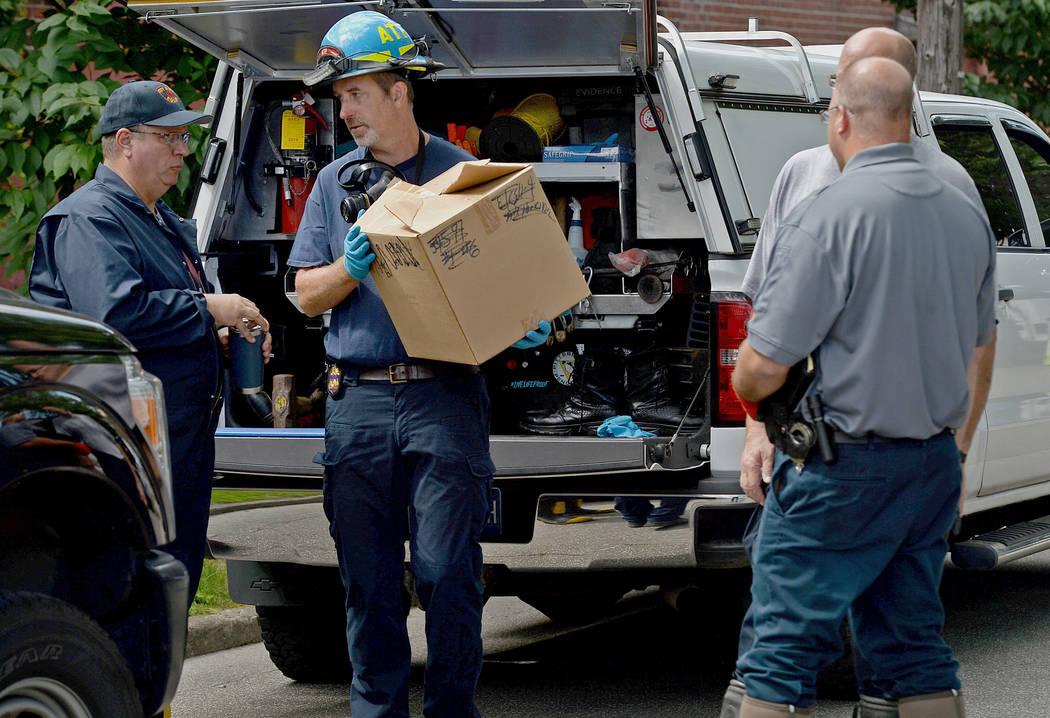 Erie Bureau of Police Det. Dave Walker, left, and Matthew Regentin, center, a fire investigator ...