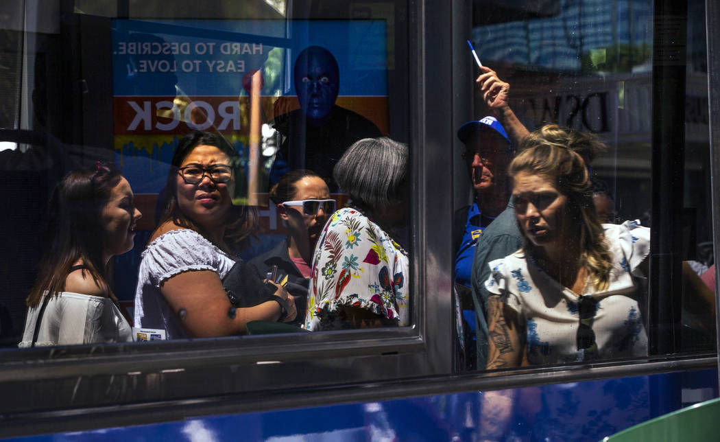 Passengers are reflected in the window of an RTC bus as they get on the bus near the MGM Grand ...
