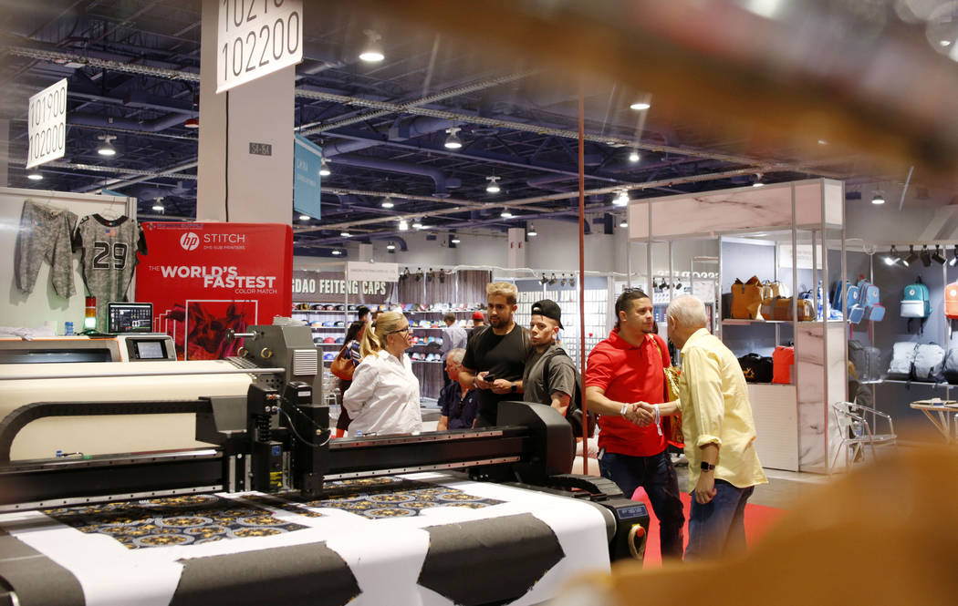 Individuals look at the Hp Stitch dye-sub printing process during the second day of the MAGIC t ...