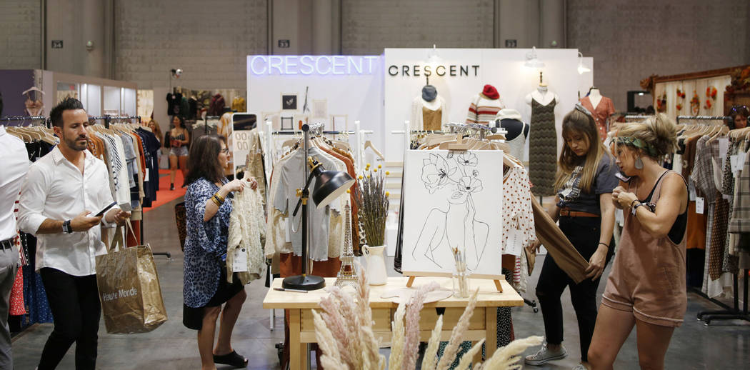 Individuals visit Crescent's exhibit during the second day of the MAGIC trade show at the Las V ...