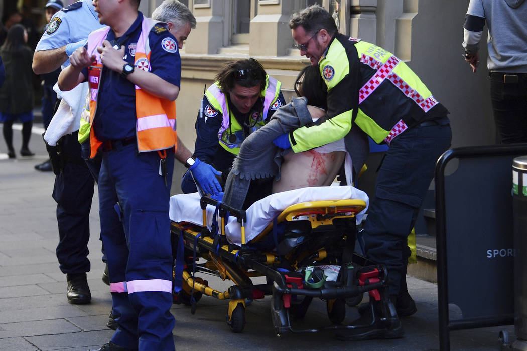 An injured woman is taken by ambulance from Hotel CBD at the corner of King and York Street in ...