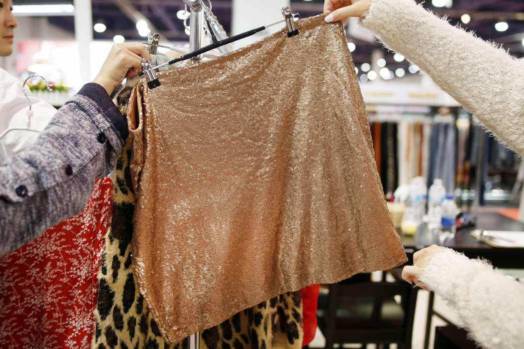 Individuals look at a sequence plus size garment at the Hayden Los Angeles exhibit during the s ...