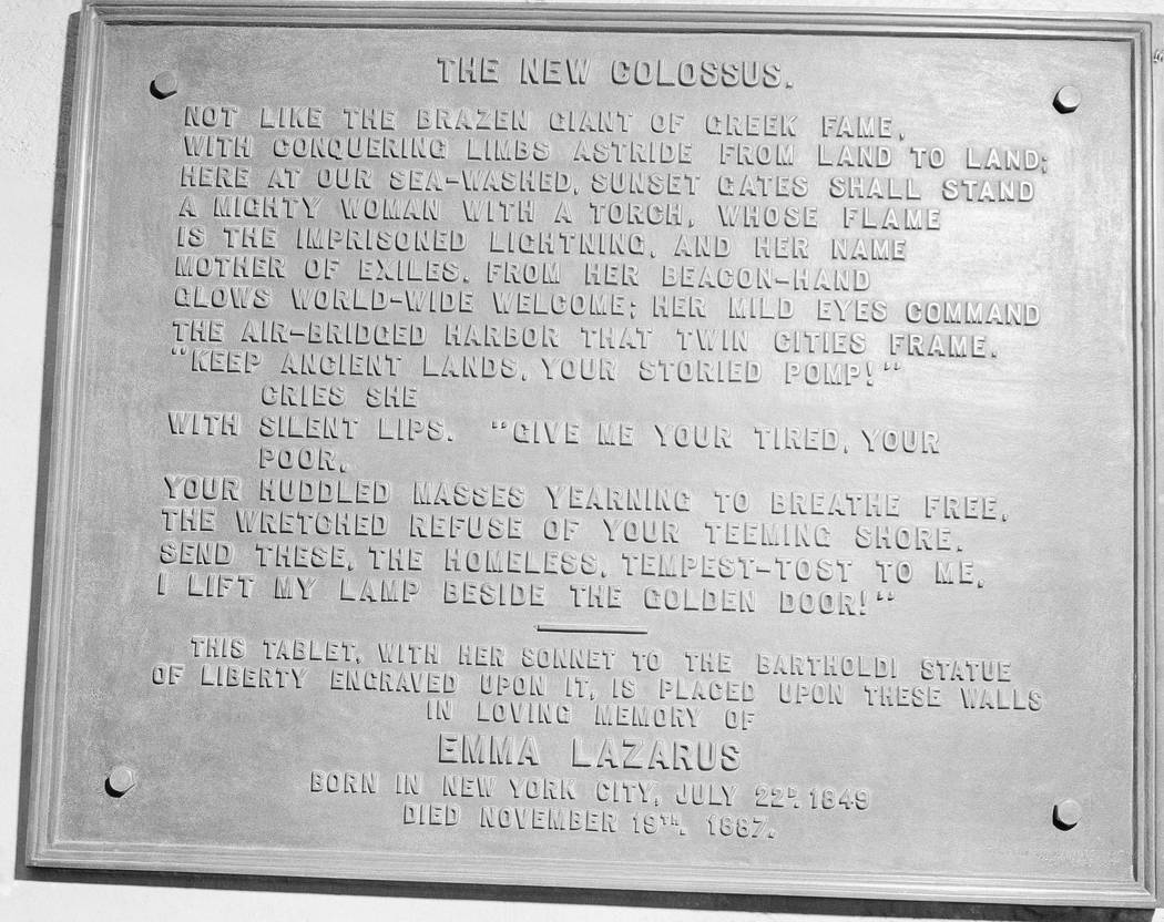FILE- In this circa 1950 photo shows a bronze plaque of the poem by Poet Emma Lazurus on Statue ...