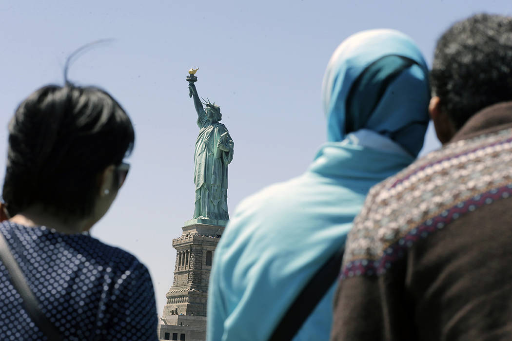 FILE - In this May 7, 2015, file photo, people look at the Statue of Liberty from a ferry boat ...