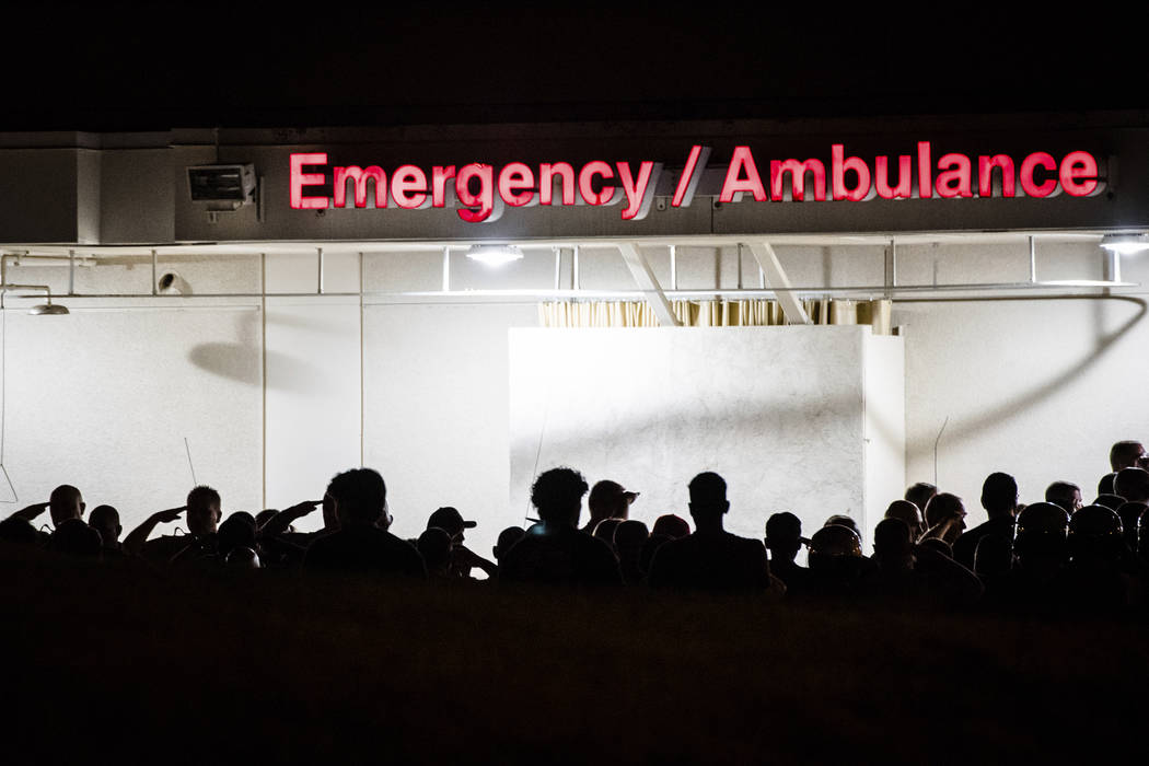 California Highway Patrol Officers gather outside the emergency room entrance to the Riverside ...