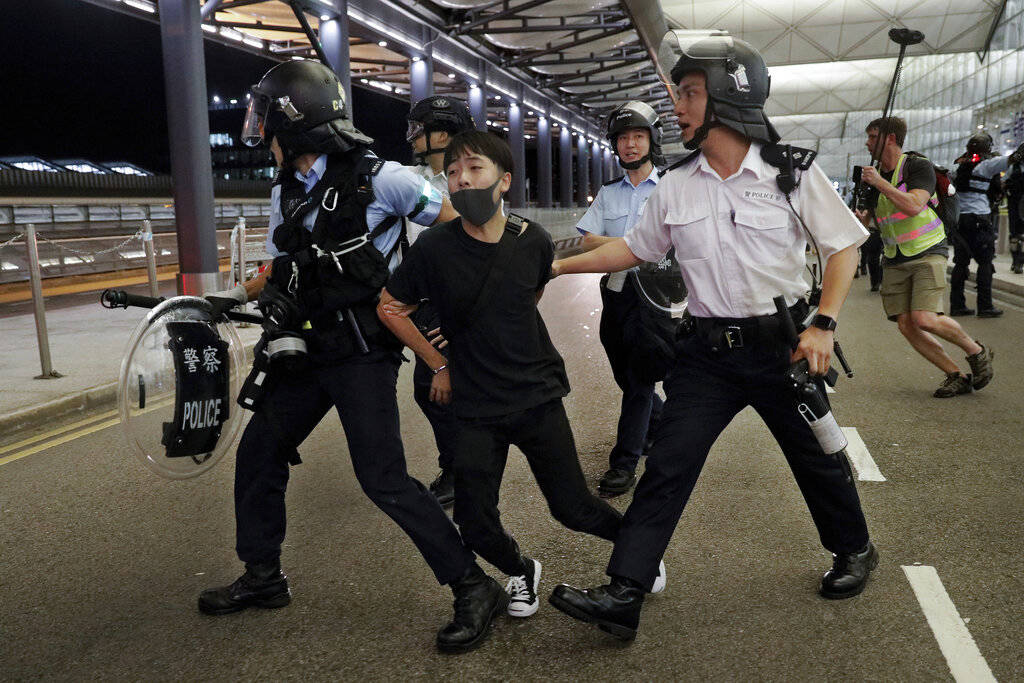 Policemen arrest a protester during a clash at the Airport in Hong Kong, Tuesday, Aug. 13, 2019 ...