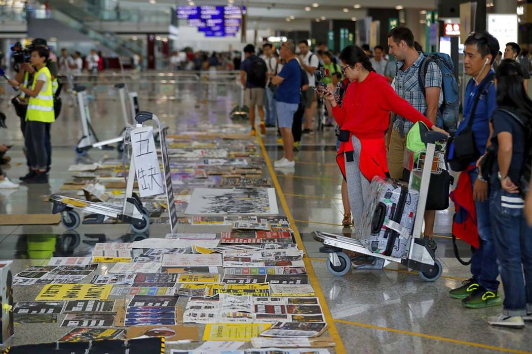 Travellers look at placards and posters placed by protesters at the airport in Hong Kong, Wedne ...