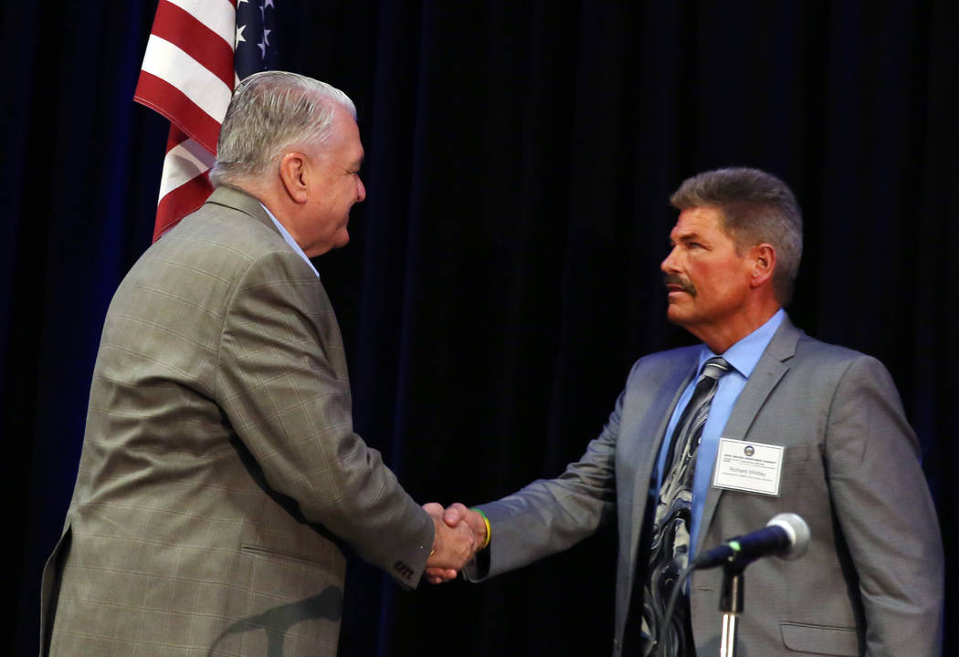 Gov. Steve Sisolak shakes hand with Richard Whitley, director of Nevada Department of Health an ...