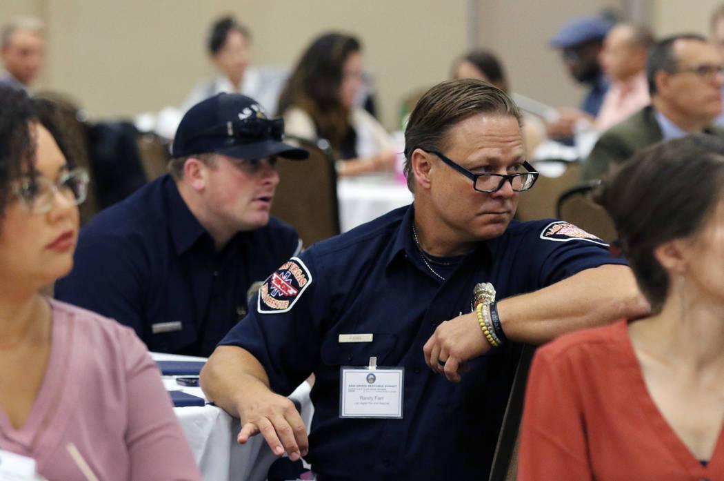 Randy Farr, second right, and Brandon Sorensen, second left, of Las Vegas Fire and Rescue atten ...