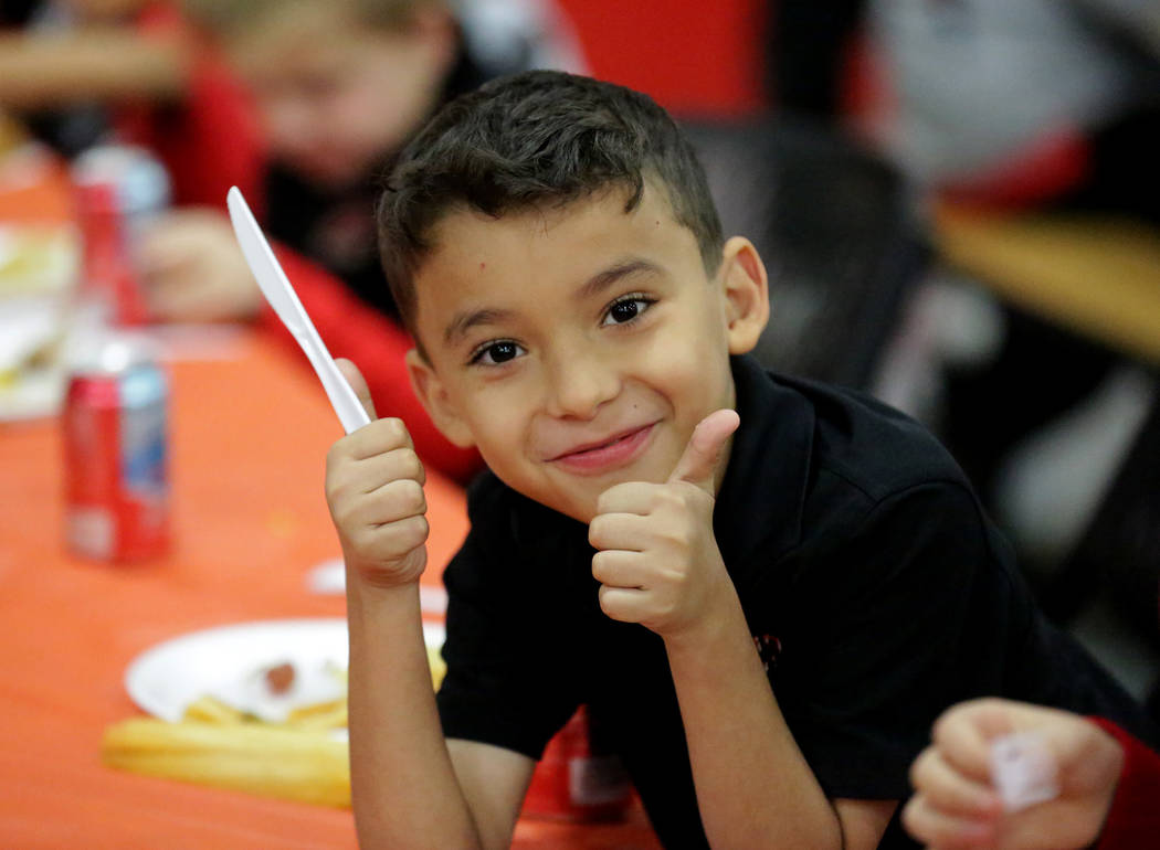 Angel Diaz, 8, gives two thumbs-up during a Thanksgiving potluck at Mountain View Christian Sch ...