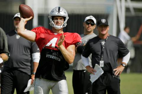 Oakland Raiders quarterback Derek Carr throws as head coach Jon Gruden, right, looks on during ...