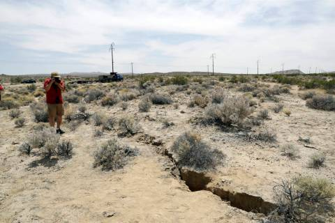 A visitor takes a photo of a crack in the ground following recent earthquakes Sunday, July 6, 2 ...
