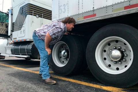 In this June 13, 2019 photo, truck driver Terry Button looks over his trailer during at stop in ...