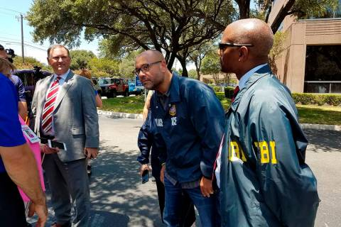 FBI agents examine the scenes Tuesday, August 13, 2019 where someone fired shots at two buildin ...