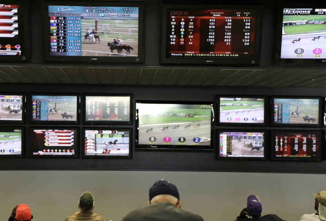 FILE - In this May 14, 2018, file photo, men watch horse racing on an array of screens at Monmo ...