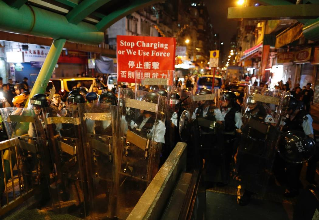Police move out from the Shum Shui Po police station to confront protesters in Hong Kong on Wed ...
