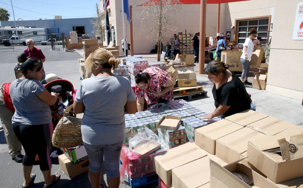 People pick up food during a food bank distribution at Veterans Village in downtown Las Vegas, ...