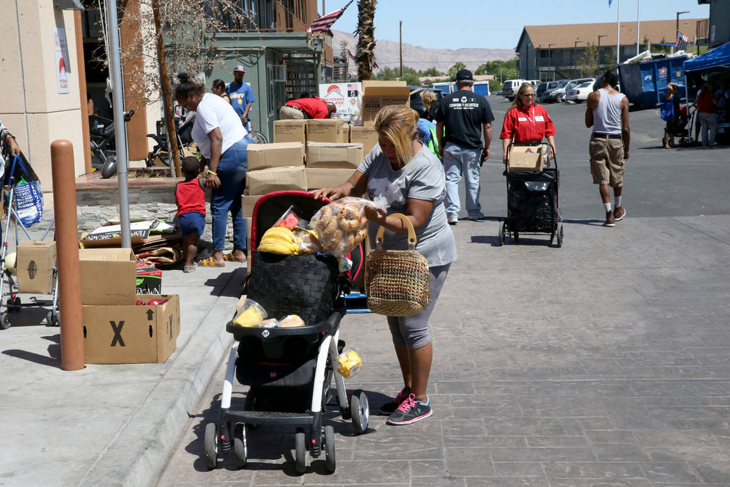 Carina Lopez picks up food during a food bank distribution at Veterans Village in downtown Las ...