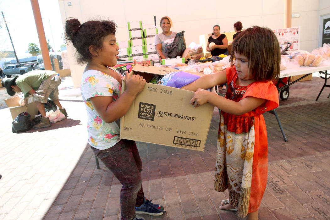 Michelle Morales, 5, left, her sister Briyit Morales, 3, and their mother Carina Lopez, rear, p ...