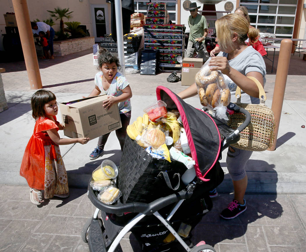Briyit Morales, 3, left, her sister Michelle Morales, 5, and their mother Carina Lopez, pick up ...