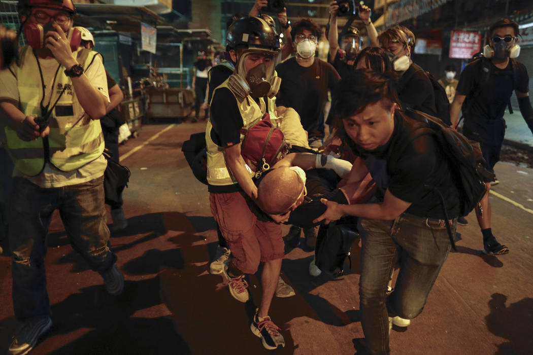 Medical staff and protesters carry an injured man as they face off with policemen near the Shum ...