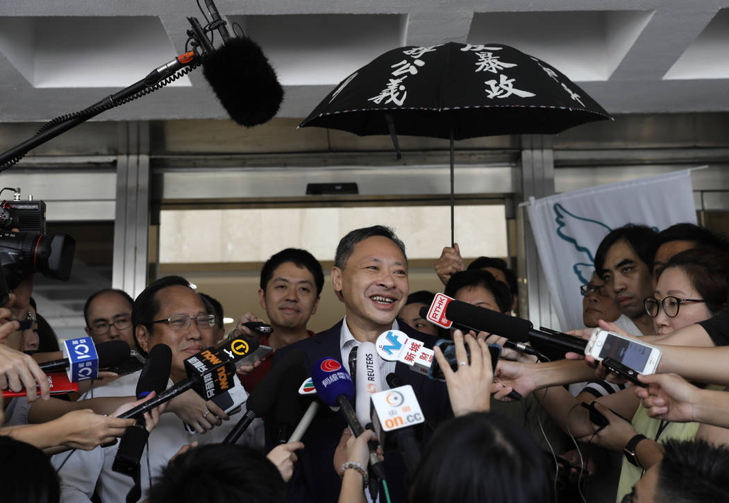 Occupy Central leader Benny Tai, center, talks to reporters outside the High court in Hong Kong ...