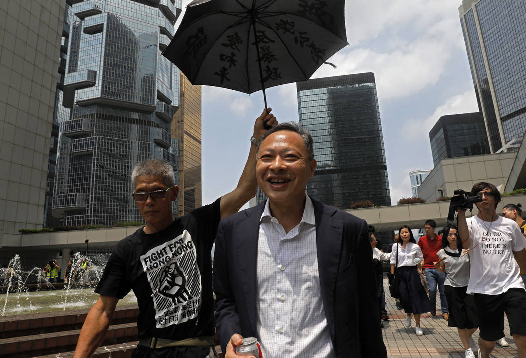 Occupy Central leader Benny Tai, center, is accompanied by a supporter who raises an umbrella a ...