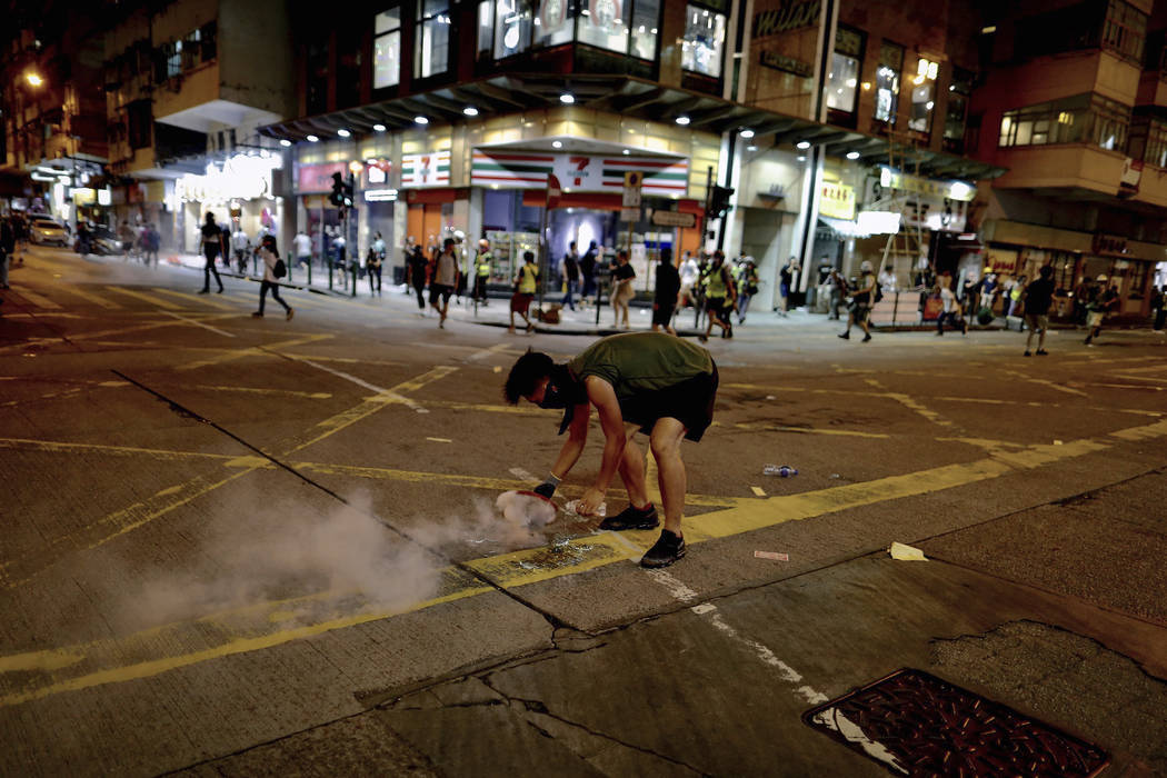 A protester uses a plate to cover a tear gas during clashes with policemen near the Shum Shui P ...