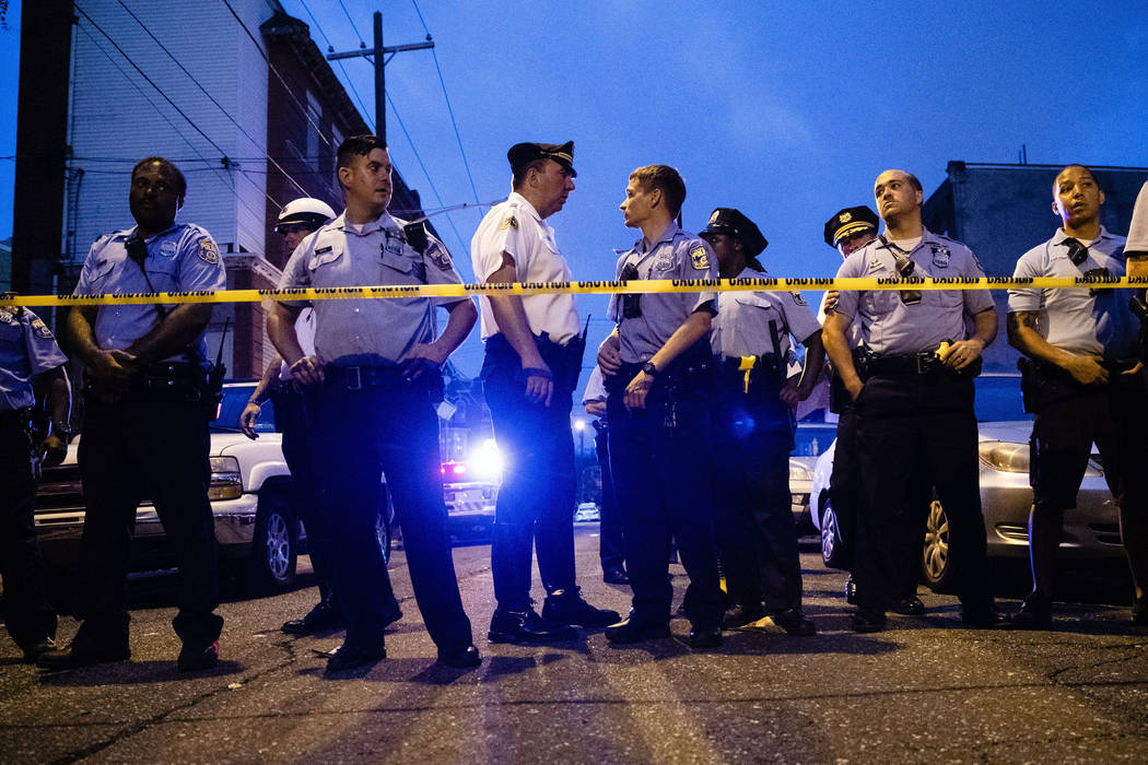 Officers gather for crowd control near a massive police presence set up outside a house as they ...