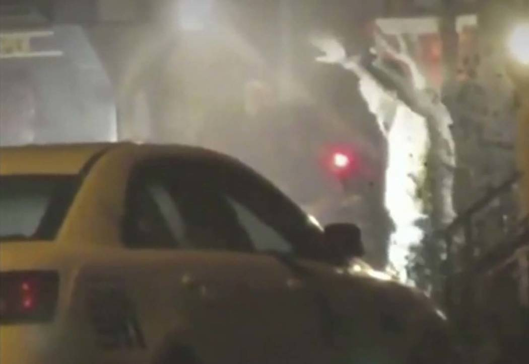 In this image from video taken by Bill Trenwith on Wednesday, Aug. 14, 2019, a man exits a buil ...