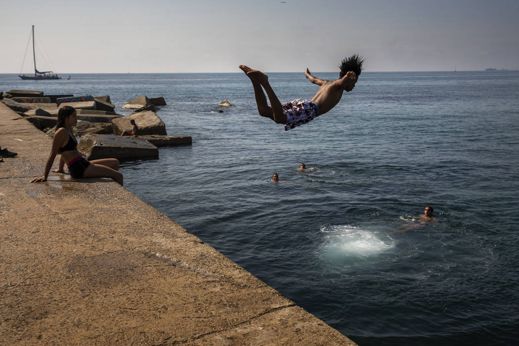 FILE - In this file photo dated Thursday, July 25, 2019, a boy jumps into the water at the beac ...