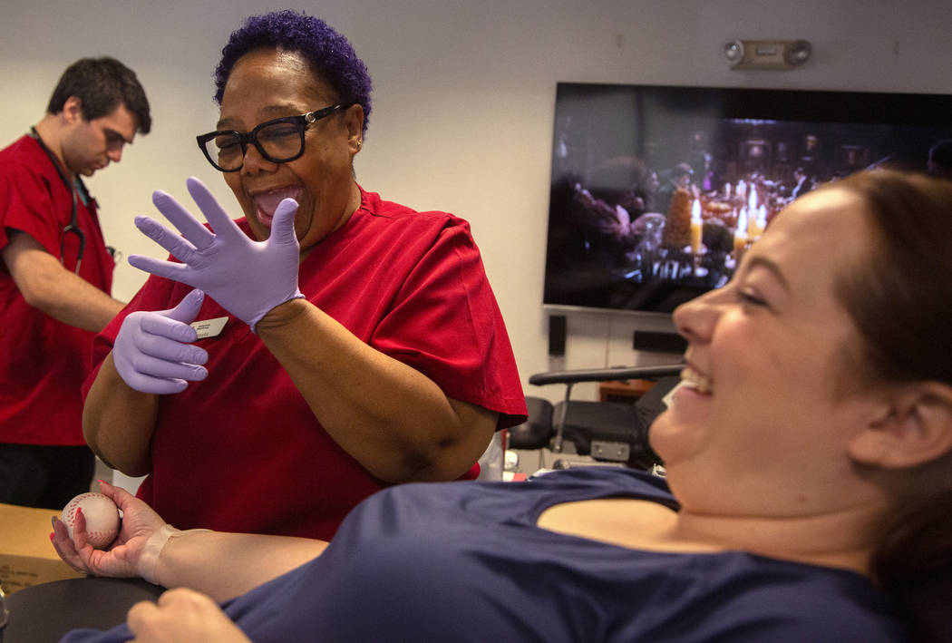Barbara Moor, 57, left, prepares to draw blood from Audra Findley, right, during the American R ...