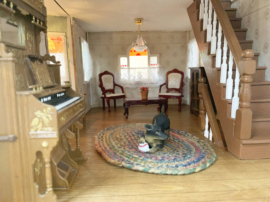 On the first floor of the dollhouse, a model dog sits in the middle of the room playing beside ...
