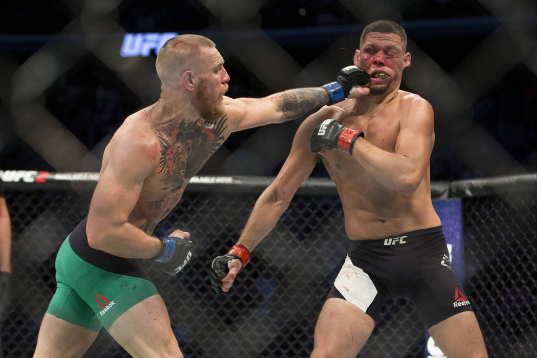 Conor McGregor, left, connects a left punch against Nate Diaz in the welterweight bout during U ...
