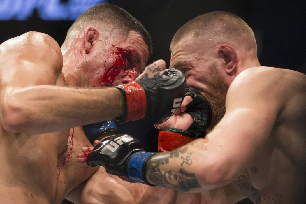 Nate Diaz, left, battles against Conor McGregor in the welterweight bout during UFC 202 at T-Mo ...