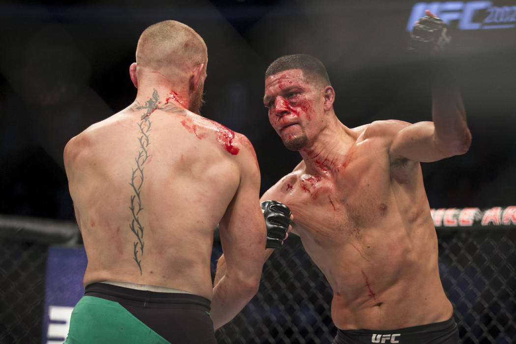 Nate Diaz, right, throws a punch against Conor McGregor in the welterweight bout during UFC 202 ...