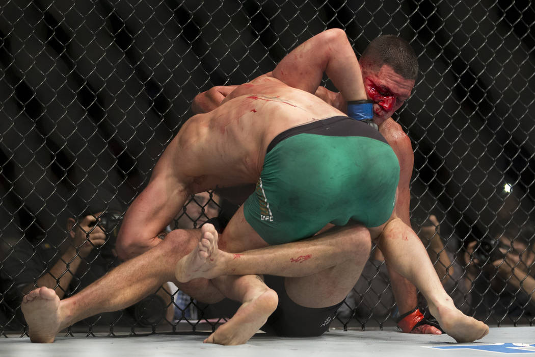 Conor McGregor, left, battles Nate Diaz in the welterweight bout during UFC 202 at T-Mobile Are ...