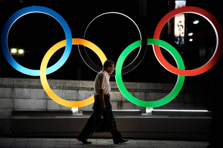 A man walks past the Olympic rings Tuesday, July 23, 2019, in Tokyo. (AP Photo/Jae C. Hong)