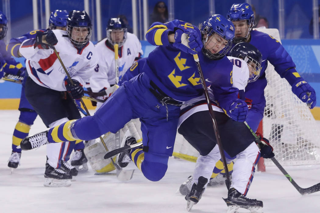 Erika Grahm (24), of Sweden, fights for control of the puck with South Korea's Choi Jiyeon (10) ...