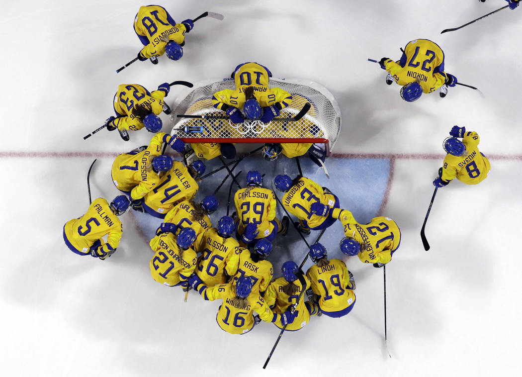 Players from Sweden gather before the preliminary round of the women's hockey game against the ...