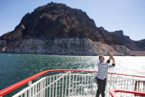 A passengers snaps photos during a mid-day sightseeing cruise of Lake Mead National Recreation ...