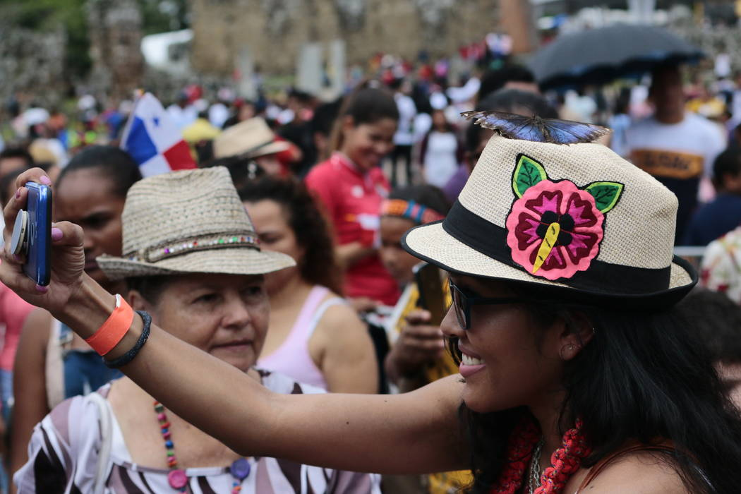 A woman takes a picture a butterfly that is standing on her hat, during the activities celebrat ...