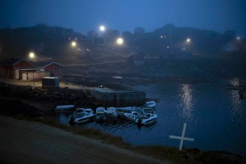 A cross sits on the side of the road as fog covers homes in Kulusuk, Greenland, early Thursday, ...