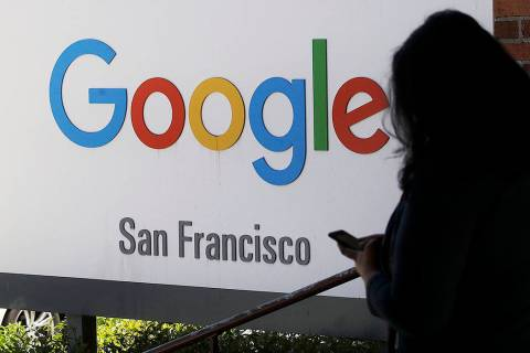 FILE - In this May 1, 2019, file photo, a person walks past a Google sign in San Francisco. Goo ...